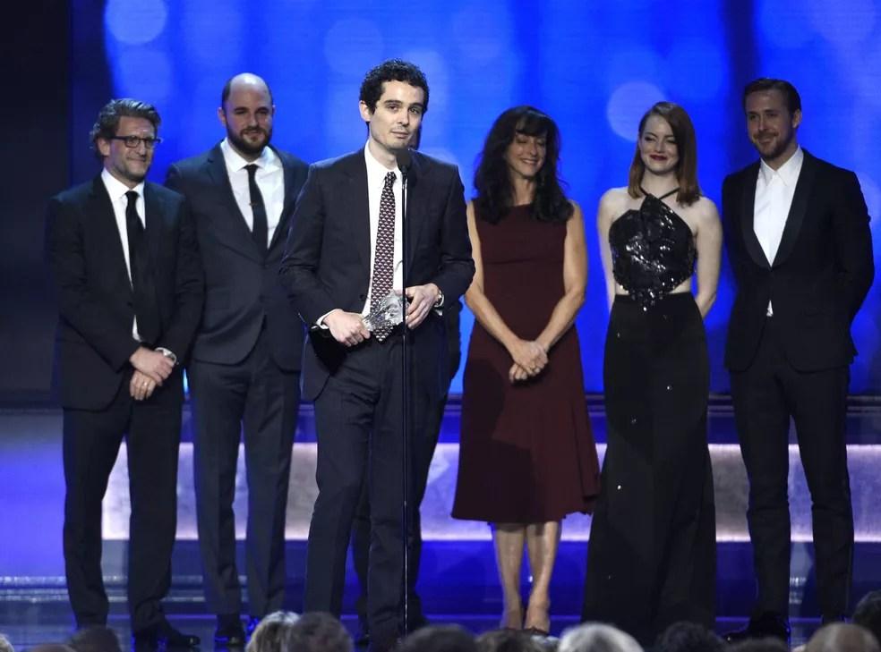 O diretor Damien Chazelle (ao centro) recebe o troféu de melhor filme no 22º Critics' Choice Awards, neste domingo (11); a partir da esquerda: Gary Bilbert, Jordan Horowitz, Chazelle, Mary Sophers, Emma Stone e Ryan Gosling (Foto: Chris Pizzello/Invision/AP)