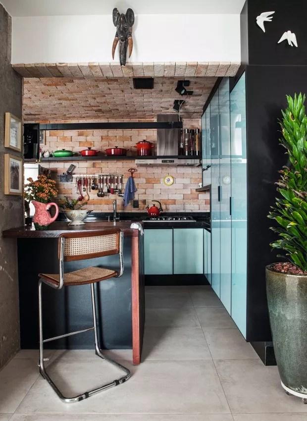 Cozinha. Mesmo pequena, tem paredes e teto revestidos por tijolos comuns e prateleiras que deixam tudo à mão (Foto: Lufe Gomes / Editora Globo)
