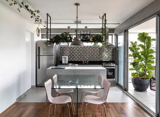 Cozinha e sala de jantar são separadas por bancada baixa e prateleira suspensa com plantas. Iluminação We Light. Mesa de jantar e produção Marche art de vie.  (Foto: Evelyn Müller/Divulgação)