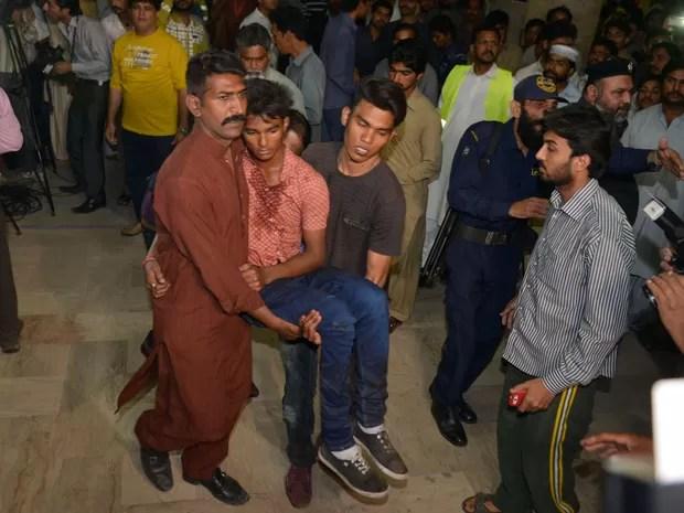 Vítima da explosão sendo socorrida depois que uma bomba explodiu em um parque público no Paquistão (Foto: Arif Ali/ AFP)