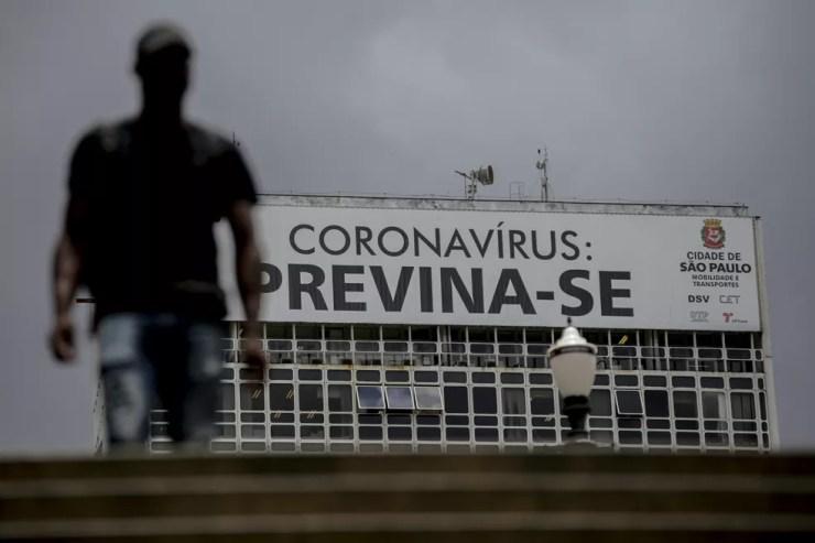 Pedestre passa por cartaz que pede prevenção contra o coronavírus, no Centro de São Paulo. — Foto: Suamy Beydoun/Estadão Conteúdo