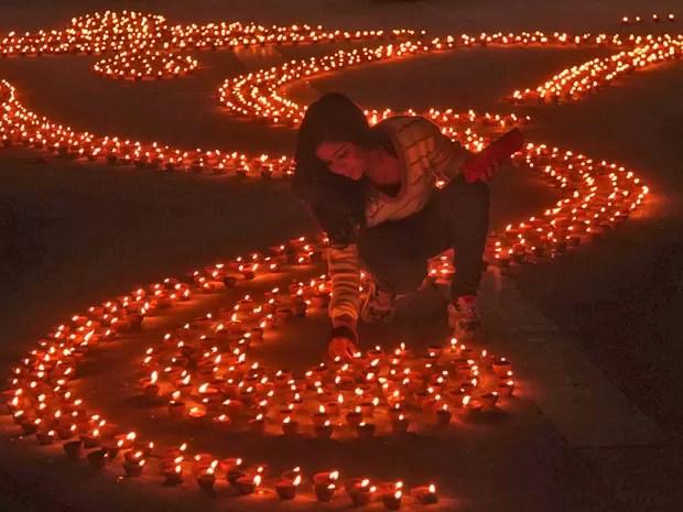 Garota acende vela na véspera do Diwali, o festival hindu das luzes, na cidade indiana de Chandigarh. (Foto: Ajay Verma/Reuters)