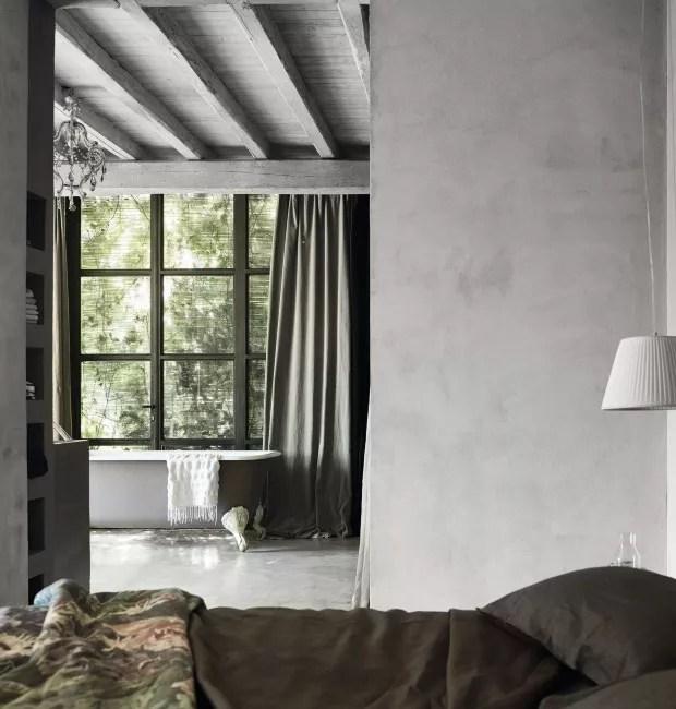 Sala de banho. Com ambientes integrados, a partir da cama é possível ver a claridade que entra pela janela do banheiro. Ao fundo, cortinas feitas de linho e banheira comprada em um antiquário em Amsterdã (Foto: Fabrizio Ciccone / Living Inside)