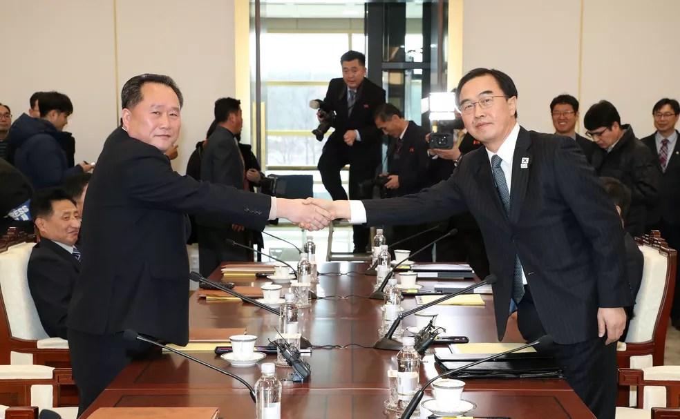 Chefe da delegação norte-coreana, Ri Son Gwon aperta a mão com o seu homólogo sul-coreano Cho Myoung-gyon durante a reunião na área desmilitarizada de Panmunjom, nesta terça-feira (9) (Foto: Yonhap via REUTERS)