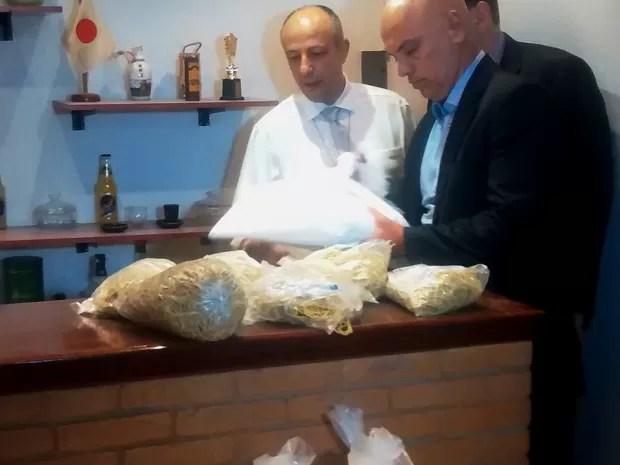 Secretário de Segurança Pública analisa cocaína apreendida pelo Denarc na noite desta sexta-feira (17) (Foto: Jamile Santana/ G1)