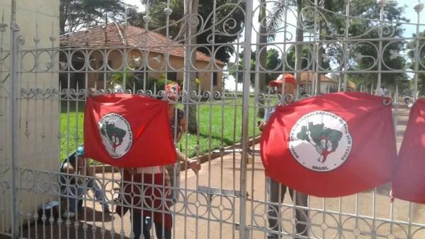 Integrantes do MST colocam bandeira do movimento no portão da fazenda de Oscar Maroni (Foto: Rodolfo Pardini/TV TEM)