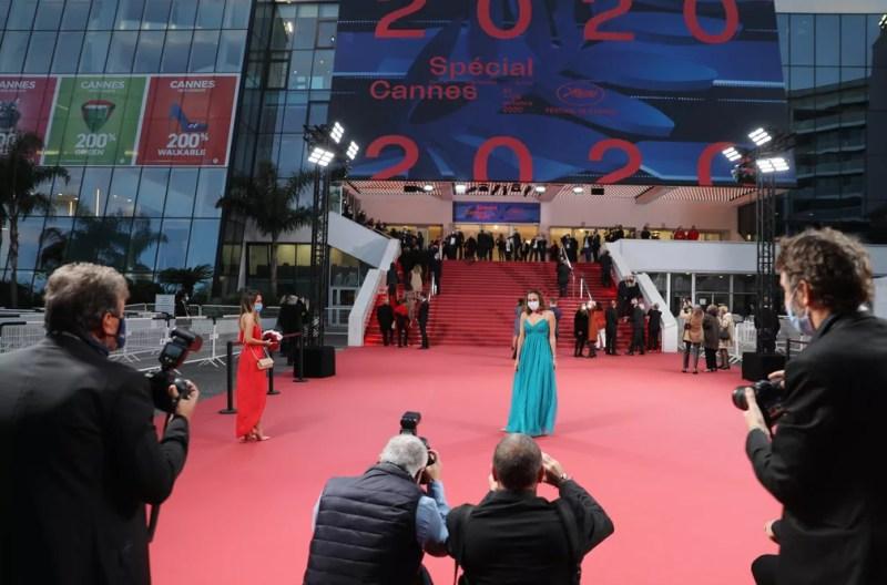 Convidados posam de máscara no tapete vermelho do Festival de Cannes — Foto: Valery Hache/AFP