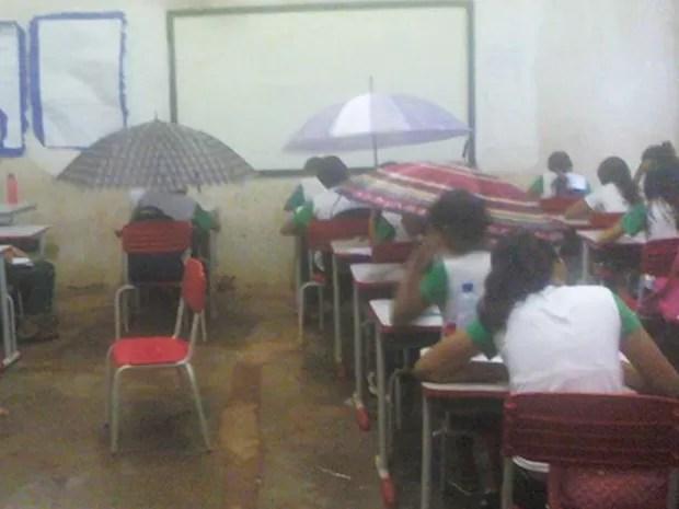 Após chuva, sala de aula das escola municipal Guilherme Dourado ficou alagada e alunos tiveram que se proteger com guarda-chuvas (Foto: Uiliene Santa Rosa)