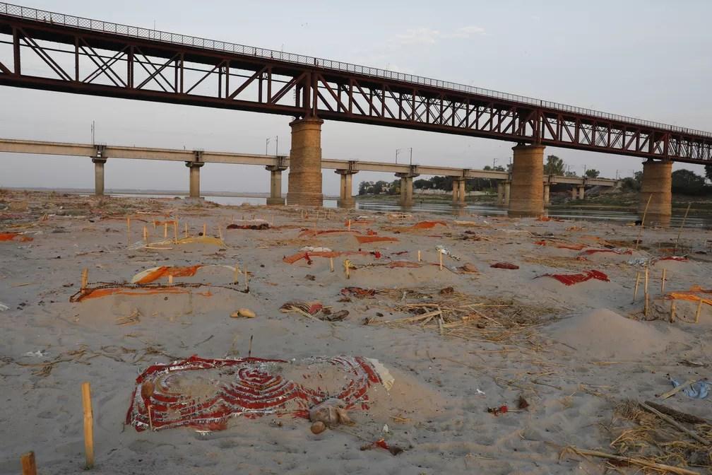 Corpos enterrados em covas rasas nas margens do Rio Ganges, perto de um local de cremação, em Prayagraj, na Índia, em 15 de maio. Suspeita é que corpos são de vítimas da Covid-19. — Foto: Rajesh Kumar Singh/AP