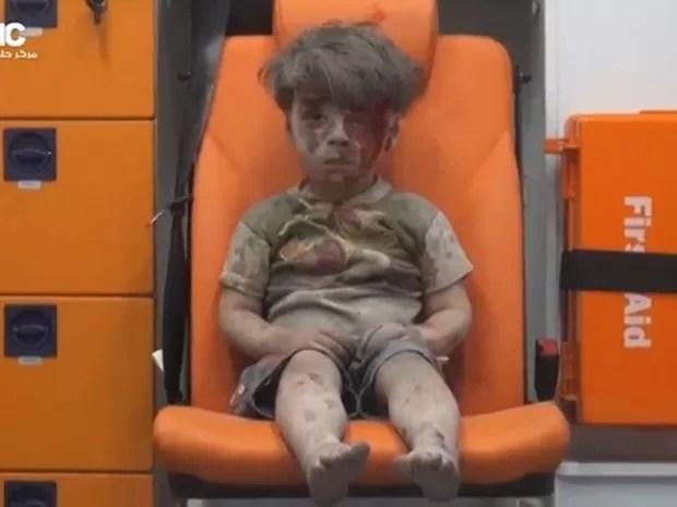 O menino Omran Daqneesh, de 5 anos, aguarda atendimento em uma ambulância, sujo de sangue e de poeira, após ser resgatado dentre escombros de um edifício alvo de um bombardeio aéreo em Aleppo, no norte da Síria. A cena causou comoção nas redes sociais (Foto: Reuters)