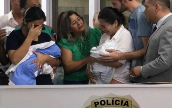 Pauliana e Aline choram ao fazer a destroca dos bebês, Trindade, Goiás — Foto: Vitor Santana/G1