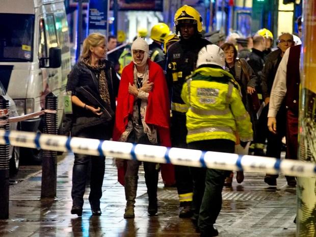 Mulher é atendida pelo serviço de emergência próximo ao Teatro Apollo, em Londres, depois do desabamento do teto. (Foto: Joel Ryan/Invision/AP)