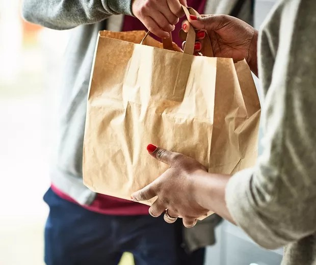 Woman holding paper bag with take out food, home delivery, food order, takeaway (Foto: Getty Images)