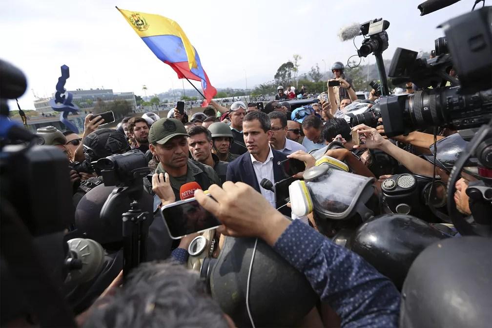 Juan Guaidó caminha em meio a apoiadores ao lado de um militar que comanda o grupo que o defende, antes de falar com a imprensa em Caracas — Foto: Fernando Llano/AP