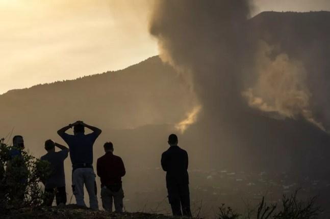 Moradores olham de uma colina enquanto a lava flui do vulcão em erupção na ilha de La Palma , na Espanha, em 24 de setembro de 2021. O vulcão nas Ilhas Canárias, um território espanhola no Oceano Atlântico, continua a produzir explosões e a expelir lava cinco dias após entrar em atividade. — Foto: Emilio Morenatti/AP