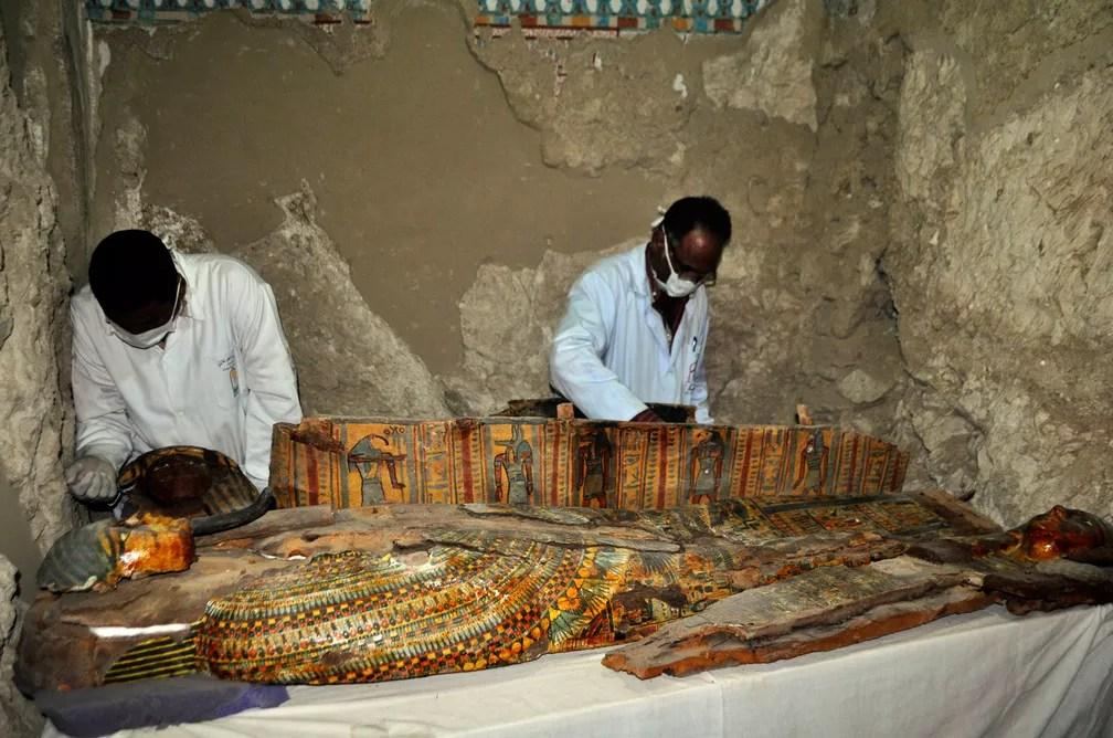 Membros da equipe de arqueólogos do Egito trabalham em sarcófago de madeira descoberto em uma tumba de 3,5 mil anos na necrópolis de Abu el-Naga, perto da cidade de Luxor, no Egito  (Foto: Stringer/AFP)