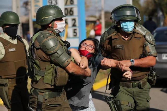 Manifestante é detida durante protesto em Santiago, no Chile, nesta segunda-feira (18) — Foto: Ivan Alvarado/Reuters