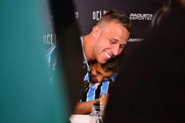Arthur abraça menino, o primeiro da fila de autógrafos (Foto: Beto Azambuja)