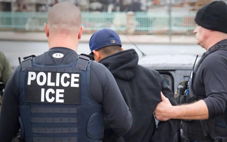 Em foto de 7 de fevereiro, agentes do Departamento de Imigração e Alfândega (ICE, na sigla em inglês) conduzem um imigrante ilegal preso em Los Angeles — Foto: Charles Reed/U.S. Immigration and Customs Enforcement via AP
