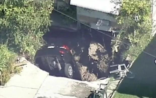 Um carro foi engolido por um buraco formado na entrada da garagem de uma casa na Flórida (Foto: BBC)