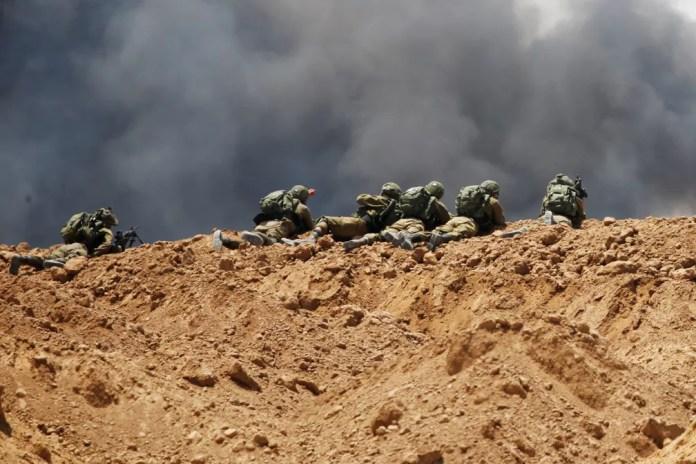 Soldados israelenses são vistos nesta segunda-feira (14) durante confronto com manifestantes na Faixa de Gaza (Foto: Baz Ratner/Reuters)