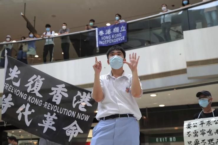 29 de maio - Manifestante gesticula com cinco dedos, significando as 'Cinco demandas - nem uma a menos', em um shopping durante protesto contra a legislação de segurança nacional da China, em Hong Kong — Foto: Kin Cheung/AP