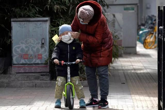 Mulher limpa o rosto de uma criança com um lenço nas ruas de Pequim, na China, nesta quinta-feira (12)  — Foto: Han Han Guan/AP