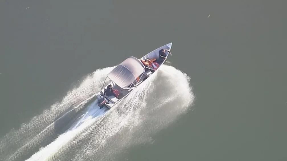 Bombeiros usam embarcação em busca por jovem desaparecida na Várzea das Flores — Foto: Reprodução/TV Globo