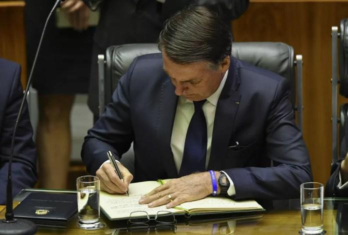 Bolsonaro assina o livro com o termo de posse dos presidentes da República — Foto: Nelson Almeida/AFP