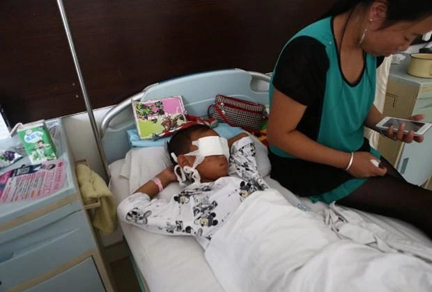 O garoto ao lado da mãe nesta terça-feira (27) em hospital da cidade chinesa de Taiyuan (Foto: AFP)