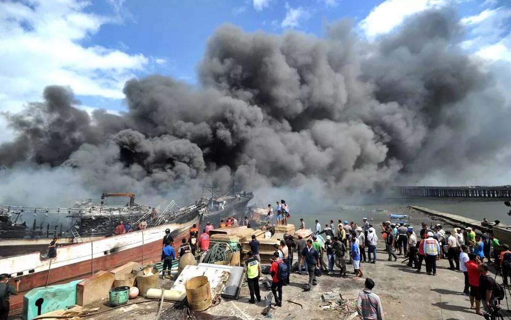 Bombeiros tentam extinguir incêndio em barcos de pesca no porto de Benoa, em Denpasar, na ilha balneária de Bali (Foto: Sonny Tumbelaka / AFP Photo)