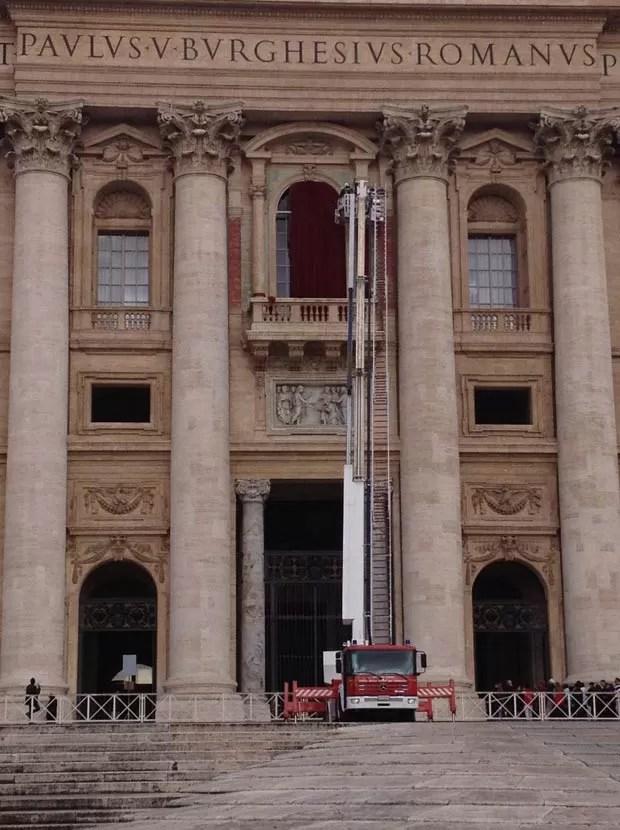 Funcionários colocam cortinas nesta segunda-feira (11) na varanda central da Basília de São Pedro, no Vaticano, onde ocorre a primeira aparição pública do novo Papa. O conclave para escolher o sucessor de Bento XVI começa nesta terça (12) (Foto: Juliana Cardilli/G1)