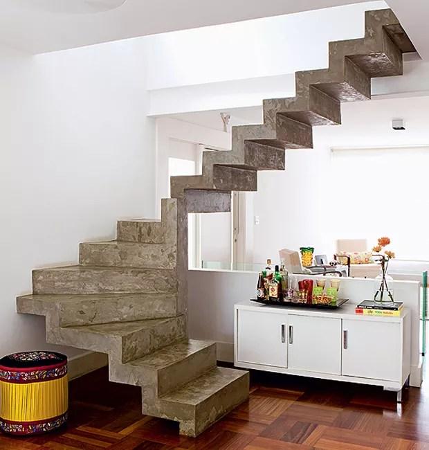 """A escada em """"L"""", que ocupava muito espaço e escurecia a sala, foi substituída por esta, em """"U"""", de concreto armado. """"A ideia era deixá-la leve e neutra. Em vez de revestimento, optamos pelo cimento queimado"""", diz a arquiteta Claudia Percego (Foto: Edu Castello/Casa e Jardim)"""