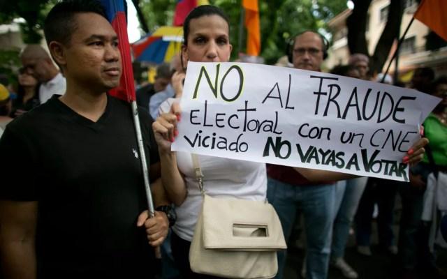 Mulher carrega um cartaz com a mensagem 'Não à fraude eleitoral com um Conselho Eleitoral Nacional viciado. Não vote' durante protesto contra as eleições presidenciais em Caracas, na Venezuela, em 16 de maio de 2018 — Foto: AP Photo/Ariana Cubillos