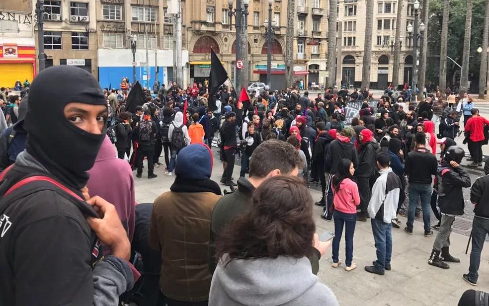Grupo de manifestantes se reúne na Praça da Sé, alguns com o rosto coberto (Foto: Marcelo Brasil/TV Globo)