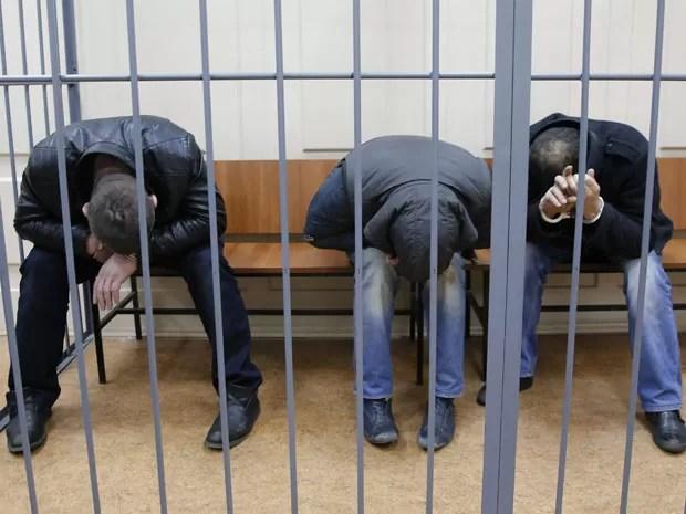 A partir da esquerda: Tamerlan Eskerkhanov, Shagid Gubashev e Ramzan Bakhayev, suspeitos do assassinato do opositor russo Boris Nemtsov, escondem o rosto em cela do tribunal de Moscou neste domingo (8) (Foto: Maxim Shemetov/Reuters)