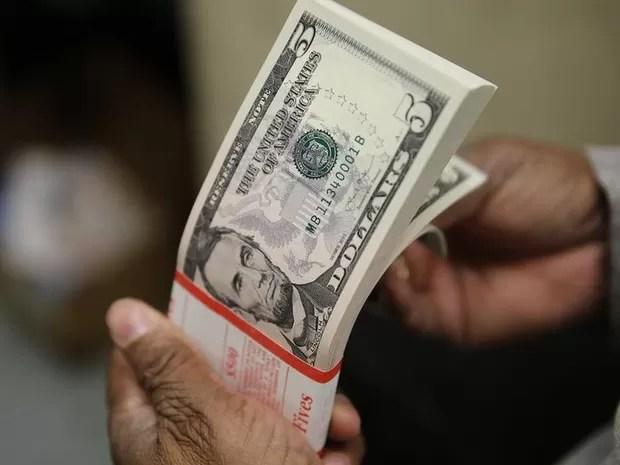 Cédulas de dólar nas mãos de uma pessoa. notas, dinheiro, dólares, cotação, câmbio, valor, economia. -HN- (Foto: Gary Cameron/Reuters)