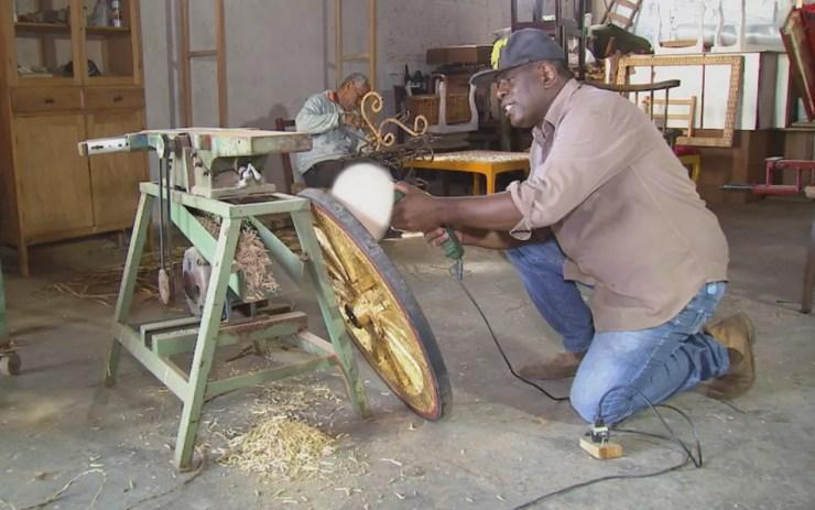 Artesão arruma a roda que conseguiu em outro Estado para montar a carruagem (Foto: Reprodução/TV TEM)