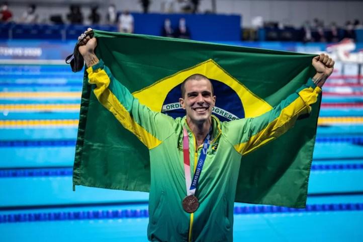 Bruno Fratus com a medalha de bronze dos 50m livre da natação nas Olimpíadas de Tóquio e a bandeira do Brasil — Foto: Jonne Roriz / COB