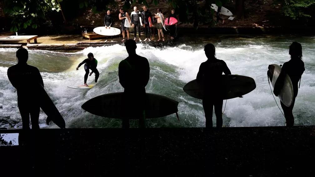 30 de maio - Surfista pega onda artificial enquanto outros aguardam sua vez no rio Eisbach, no Jardim Inglês, zona central de Munique, na Alemanha (Foto: Matthias Schrader/AP)