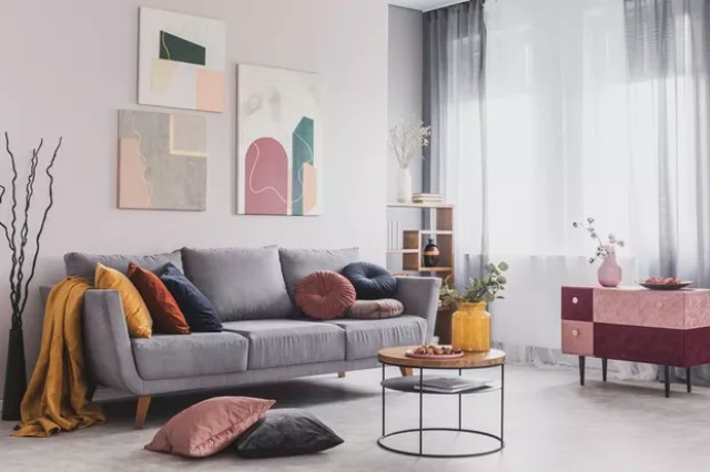 Real photo of abstract paintings hanging on white wall above a gray sofa in a living room interior with big windows (Foto: Getty Images/iStockphoto)