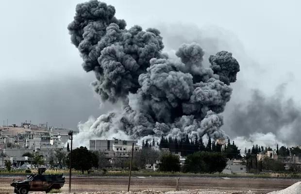 Ataque a Kobane visto da fronteira turco-síria, no vilarejo de Mursitpinar, neste domingo (12) (Foto: Aris Messinis/AFP)