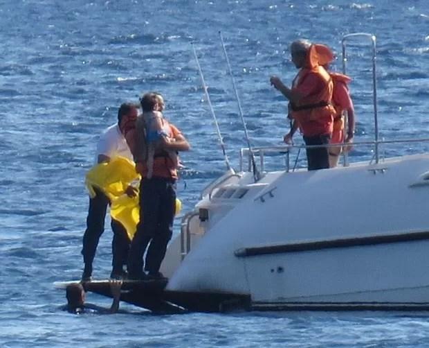 Momento em que a criança é resgatada e trazida a bordo da lancha da Guarda Costeira (Foto: Hanife Erdinc/Anadolu Agency/AFP)