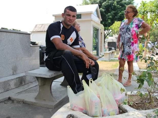 Fábio Olavo é mototaxista, mas na véspera e no Dia de Finados vende velas para conseguir renda extra (Foto: Adneison Severiano/G1 AM)