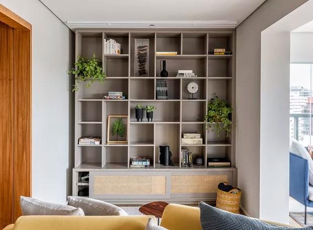 Estante | A estante com fundo em porcelanato é a primeira visão de quem entra no apartamento e foi uma solução para criar um plano de fundo interessante à mesa de jantar (Foto: Renato Navarro/Divulgação)