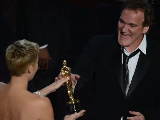 Quentin Tarantino recebe, das mãos de Charlize Theron, o Oscar de melhor roteiro original por 'Django livre' (Foto: Robyn Beck/AFP)