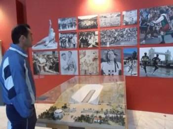 Corredor observa painel de fotos de maratonistas famosos, como Vanderlei Cordeiro de Lima (no alto, à direita). Fotos de Manoela Penna (Foto: Arquivo)