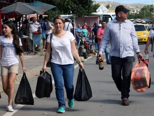 Venezuelanos compram alimentos e remédio na Colômbia neste domingo (10); fronteira foi aberta por 12 horas (Foto: Manuel Hernandez/Reuters)