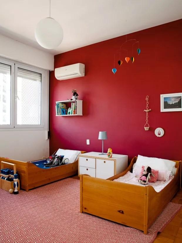 Quarto das crianças. Os filhos do casal dividem o mesmo dormitório, onde uma das paredes foi pintada em um tom de vermelho. Entre as camas há um pequeno móvel desenhado pelos arquitetos. Na parede, destaque para o bordado redondo (Foto: Maíra Acayaba / Editora Globo)