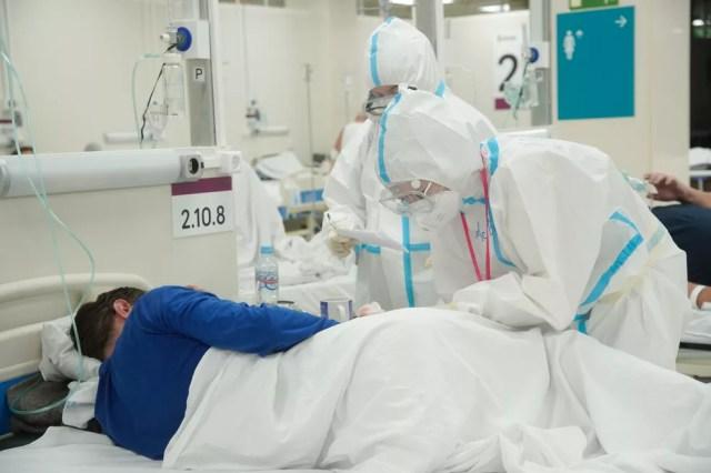 Profissionais de saúde usando equipamentos de proteção individual cuidam de paciente com Covid-19 em hospital de campanha em Moscou, na Rússia, no dia 30 de outubro. — Foto: Alexander Avilov/Moscow News Agency/Handout via Reuters